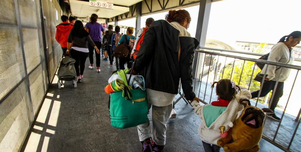 Madres y niños de la caravana migrante cruzan el puente peatonal